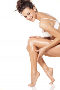 smiling beautiful young woman apply lotion on her legs